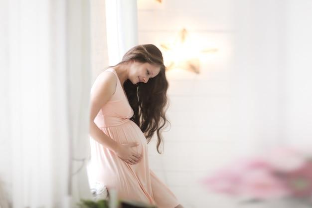 Piękna kobieta w ciąży w pobliżu okna, styl życia