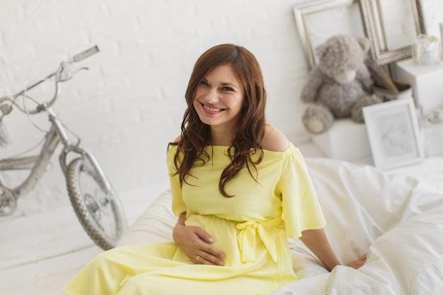 Piękna kobieta w ciąży w żółtej sukience w studio.