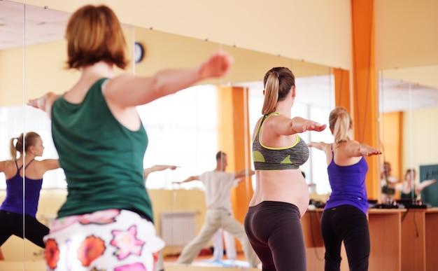 Piękna kobieta w ciąży wykonuje ćwiczenia aerobowe lub asany z grupą jogi w centrum fitness