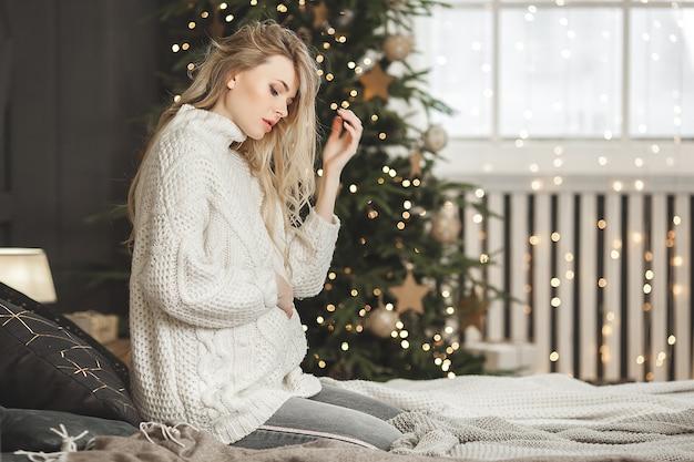 Piękna kobieta w ciąży z dekoracją świąteczną