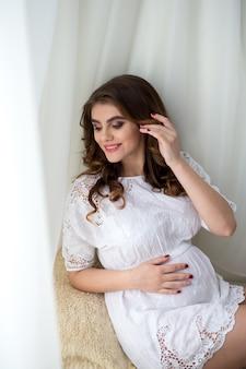 Piękna kobieta w ciąży z doskonałym makijażem i fryzurą, ubrana w białą sukienkę, siedząca na kanapie