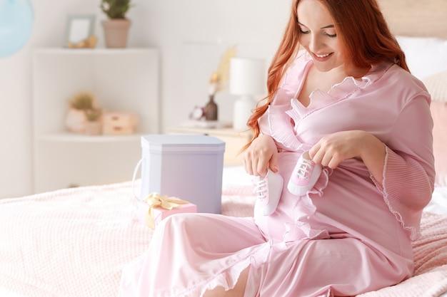 Piękna kobieta w ciąży z prezentami baby shower w domu