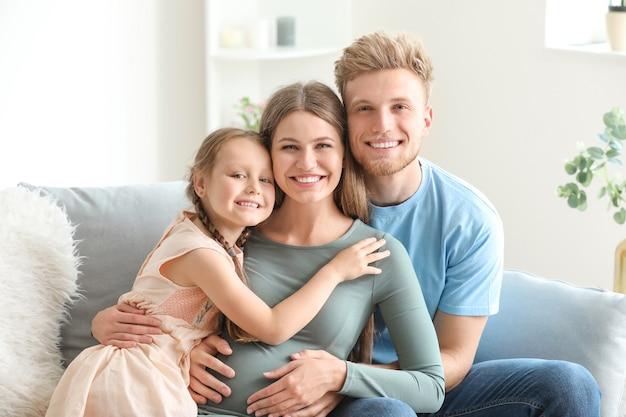 Piękna kobieta w ciąży z rodziną w domu