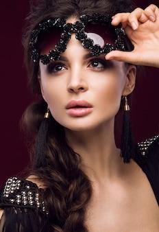 Piękna kobieta w ciemnych okularach przeciwsłonecznych, z lokami i wieczorowym makijażem