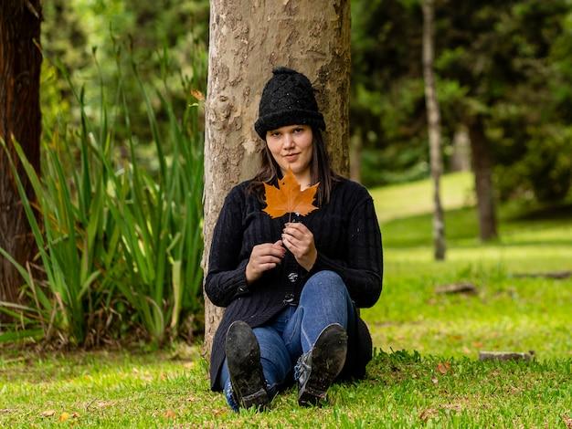 Piękna kobieta w czapka zimowa w pochmurny dzień, siedząc na trawniku w parku obok drzewa