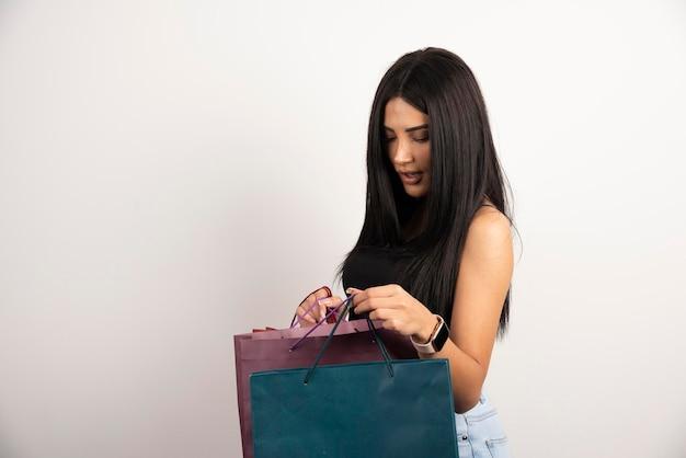 Piękna kobieta w czarnej górze patrząc na torby na zakupy. wysokiej jakości zdjęcie
