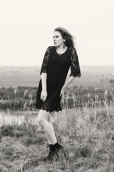 Piękna kobieta w czarnej koronkowej sukience na łące na wzgórzu nad rzeką w odcieniach szarości