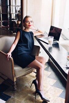 Piękna kobieta w czarnej krótkiej sukience siedzi na krześle w kawiarni. ona patrzy do kamery.