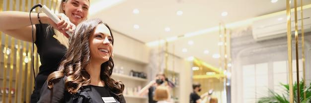 Piękna kobieta w czarnej sukience siedzi na krześle fryzjerskim i uśmiecha się doświadczonej