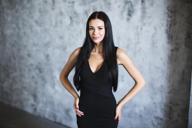 Piękna kobieta w czarnej sukni. na ciemnym tle.