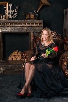 Piękna kobieta w czarnej sukni z gorsetem siedzi na krześle w czerwonych butach