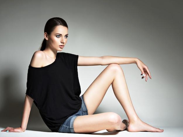 Piękna kobieta w czarny t-shirt i niebieskie dżinsy szorty.