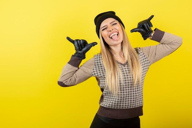 Piękna kobieta w czarnych rękawiczkach i kapeluszu pozuje na żółto.