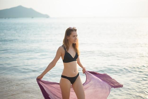 Piękna kobieta w czarnym bikini spaceruje po plaży