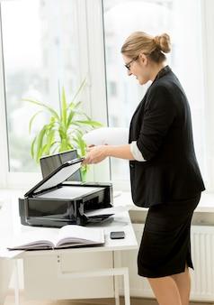 Piękna kobieta w czarnym garniturze korzystająca z drukarki na stole