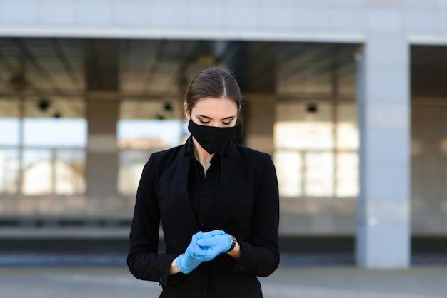 Piękna kobieta w czarnym garniturze w czarnej masce medycznej i rękawiczkach w mieście w kwarantannie i izolacji. pandemia covid-19. obraz z selektywną ostrością