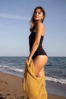 Piękna kobieta w czarnym stroju kąpielowym na plaży