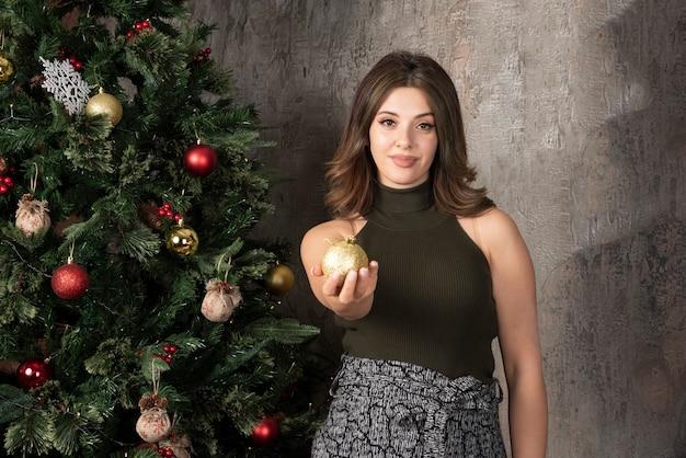 Piękna kobieta w czarnym topie pozuje ze złotą piłką w pobliżu choinki
