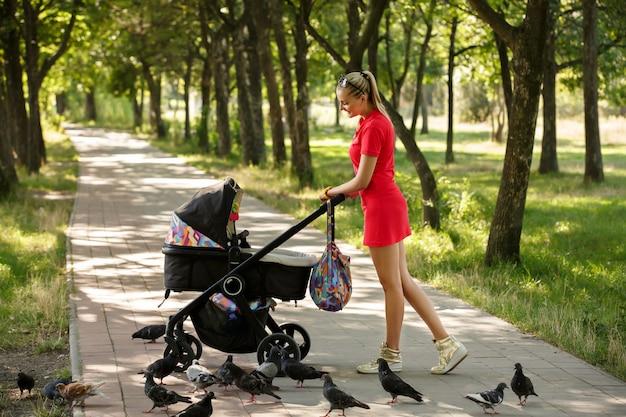 Piękna kobieta w czerwieni sukni odprowadzeniu z spacerowiczem w parku