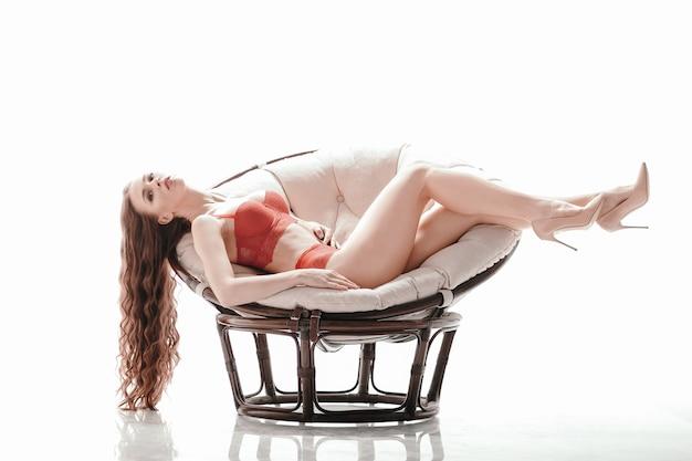 Piękna kobieta w czerwonej bieliźnie leżąca w eleganckim krześle. na białym tle