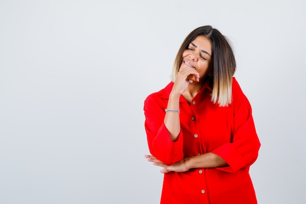 Piękna kobieta w czerwonej bluzce trzymając rękę na brodzie, zamykając oczy i patrząc spokojnie, widok z przodu.