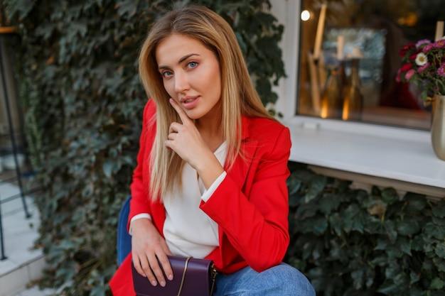Piękna kobieta w czerwonej kurtce, odpoczynek w kawiarni ulicy