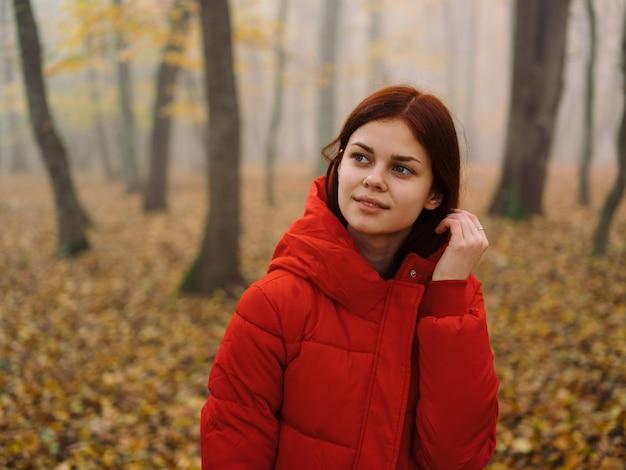Piękna kobieta w czerwonej kurtce w lesie jesienią w przyrodzie