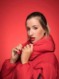 Piękna kobieta w czerwonej kurtki pozie