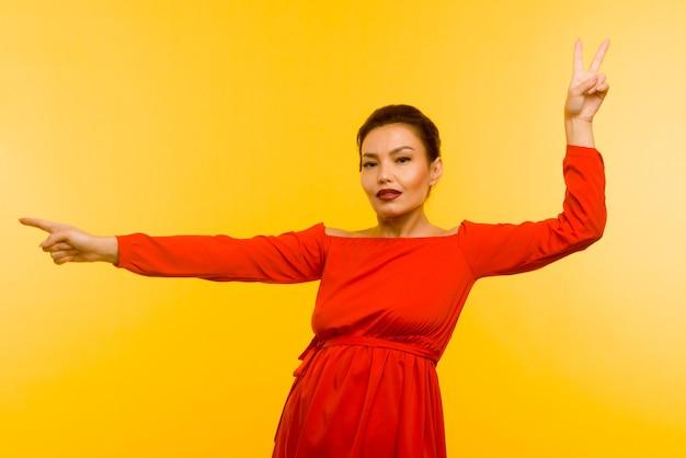 Piękna kobieta w czerwonej sukience wskazując palcem na żółtym tle