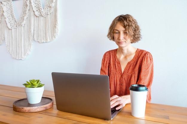 Piękna kobieta w czerwonej sukience za pomocą laptopa siedząc w kawiarni pojęcie pracy na odległość