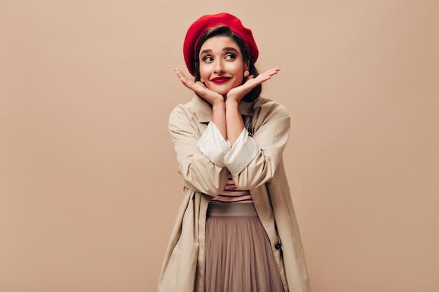 Piękna kobieta w czerwonym kapeluszu i okopie pozuje na beżowym tle. ładna dziewczyna z czerwonymi, jasnymi ustami w stylowym płaszczu przeciwdeszczowym i berecie odwraca wzrok.