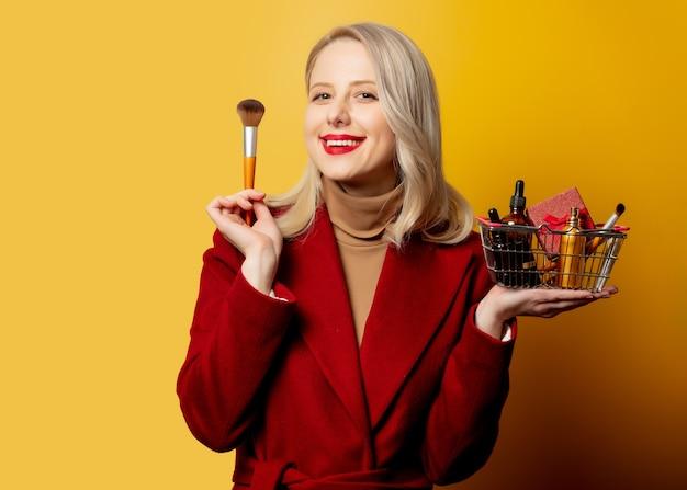 Piękna kobieta w czerwonym płaszczu z koszem pełnym kosmetyków na żółtej ścianie