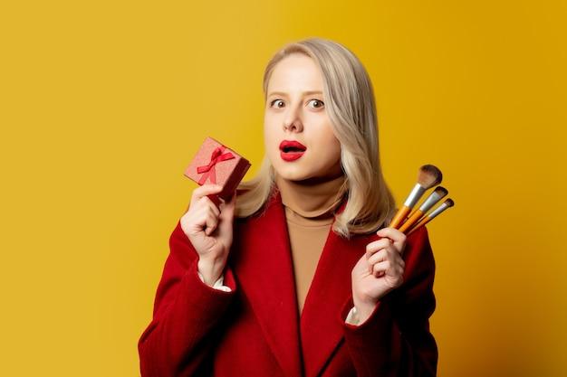 Piękna kobieta w czerwonym płaszczu ze szczotkami i pudełko na żółtej ścianie