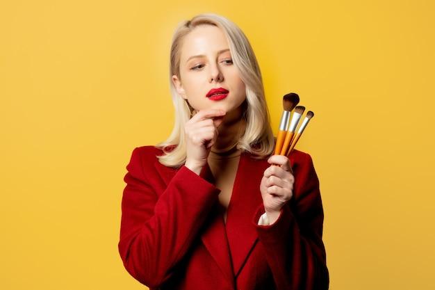 Piękna kobieta w czerwonym płaszczu ze szczotkami na żółtej ścianie
