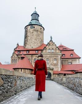 Piękna kobieta w czerwonym płaszczu zostaje w pobliżu zamku