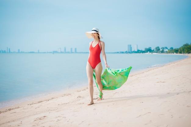 Piękna kobieta w czerwonym stroju kąpielowym spaceruje po plaży
