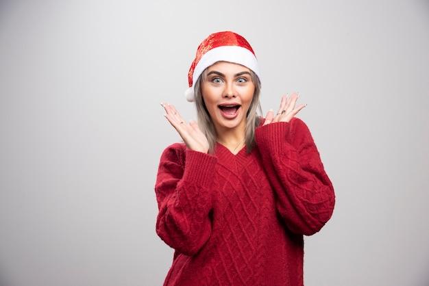 Piękna kobieta w czerwonym swetrze zdziwiona swoim prezentem.