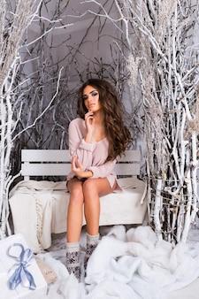 Piękna kobieta w delikatnym różowym swetrze o idealnej sylwetce, siedząca na jasno udekorowanym tarasie.
