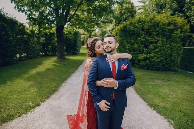 Piękna kobieta w długiej czerwonej sukni chodzi z mężem po mieście