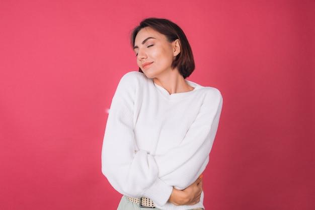 Piękna kobieta w dorywczo biały sweter, koncepcja miłości, trzymając ręce skrzyżowane przytulanie się z zamkniętymi oczami