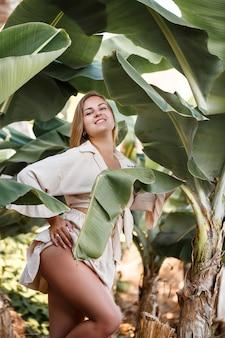 Piękna kobieta w dżungli. ośrodek lub hotel z tropikalnymi drzewami i roślinami. kobieta z blisko bananowym liściem. dziewczyna na wakacjach w lesie deszczowym. selektywne skupienie