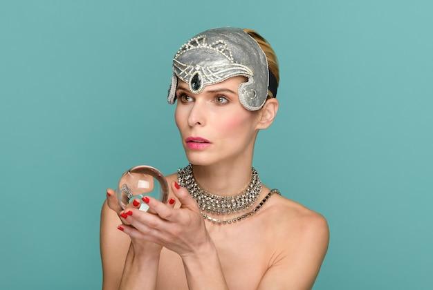 Piękna kobieta w eleganckiej tiara i naszyjniku pokazująca przezroczystą szklaną kulę i odwracającą wzrok w zdumieniu na turkusowym tle