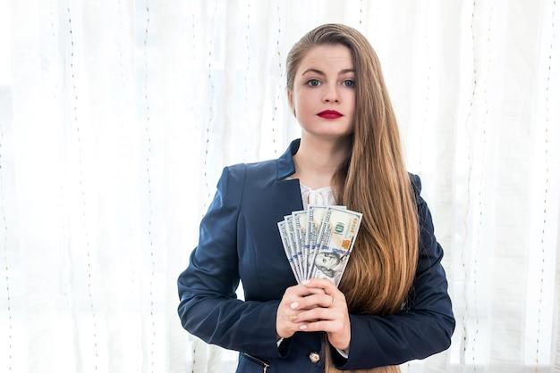 Piękna kobieta w garniturze pokazująca banknoty dolarowe