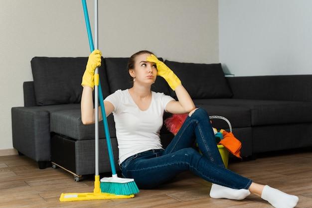 Piękna kobieta w gumowych rękawiczkach obok płaszcza i środków czyszczących złości się na wiele prac domowych