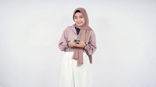 Piękna kobieta w hidżabie gra na smartfonie szczęśliwie na białym tle