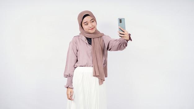 Piękna kobieta w hidżabie podejmująca działania przed kamerą przed telefonem słodkie uśmiechnięte wyrażenie na białym tle