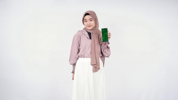 Piękna kobieta w hidżabie pokazująca ekran smartfona na białym tle