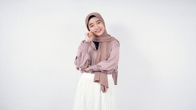Piękna kobieta w hidżabie pozuje szczęśliwie na białym tle