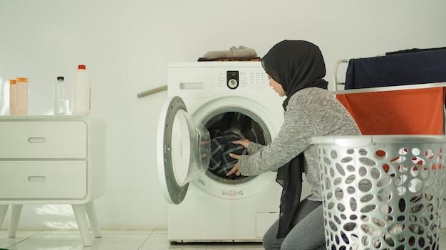 Piękna kobieta w hidżabie pranie w pralce w domu