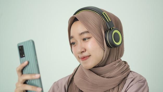 Piękna kobieta w hidżabie radośnie patrzy na swój telefon komórkowy